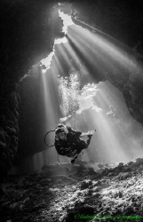 Cathedral lighting illuminates diver inside a cave at St ... by Gabriel De Leon Jr